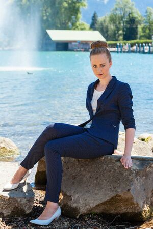 pantsuit: Full Length Portrait of Young Woman Wearing Blue Business Suit Sitting on Large Rock Boulder by Lake and Staring Seriously at Camera on Bright Sunny Day