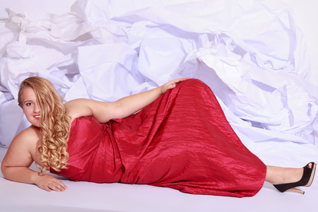 court shoes: Full length portrait of a beautiful plus size curly young blond woman posing on white in red dress and court shoes. Stock Photo