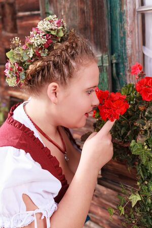 flower boxes: Portrait of a young chubby woman in red dirndl, you smelling a geranium in a flower boxes beneath a window Stock Photo