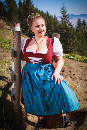 Portrait of a young peasant woman thick in the mountains in festive costume and big bust, with braided hair and hair wreath of flowers on her head. In the background of the Tyrolean Alps.