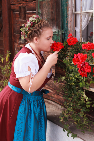 girl boobs: Young, Bavarian, chubby girl in red dirndl smelling a geranium in a flower box below a window of an old farmhouse with wood built