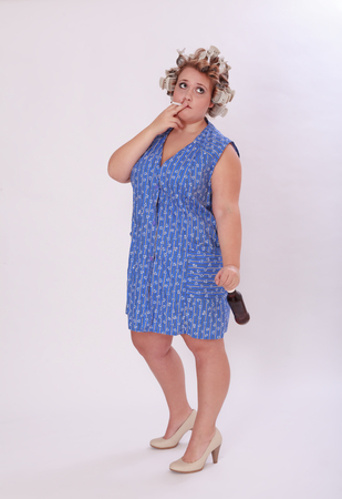 hair curler: Full Length Shot of a Thoughtful Chubby Woman with Hair Curler Smoking a Cigarette While Looking Against Gray Background.