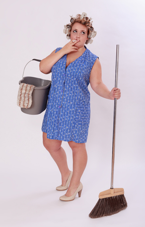 hair curler: Full Length Shot of a Funny Smoking Household Help with Hair Curler, Holding Pail and Broom While Looking Up Against Gray Background. Stock Photo