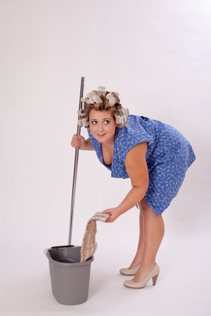 hair curler: Young Female Cleaner with Hair Curler Wearing Shoes, Holding Cleaning Materials, Looking Into the Distance Against Gray Background. Stock Photo