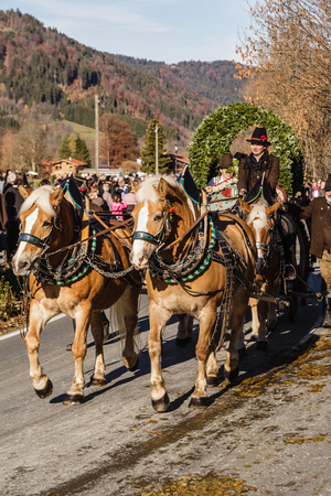 patron: Schliersee, Germany - November 8, 2015: Every year on the 1st Sunday in November the Idillically horse procession, named Leonhardi Bavarian Schliersee in commemoration of the patron St. Leonhard instead. Floats with people dressed in traditional clothing, Editorial