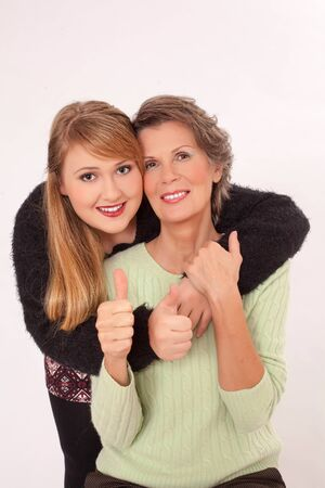 voluptuous: Young woman with voluptuous curves hugging her grandmother, both positive and think with thumbs up