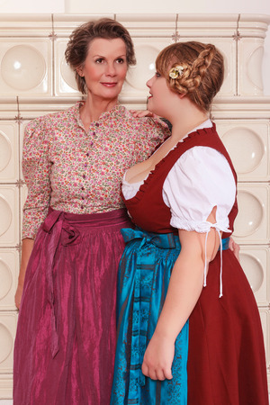 two generations: Two generations of women in dirndl with beautiful hairstyle in front of a fireplace Stock Photo