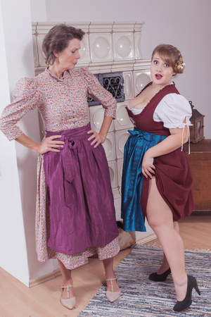 Grandmother appalled by the behavior of Their granddaughter, who pulls up the skirt of her dress to her waist and her bare leg showing. Stockfoto