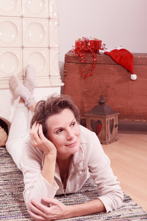 warms: Senior lying on the ground on a carpet and warms your feet on a hot fireplace, with views to the side. In the background Christmas decoration. Stock Photo