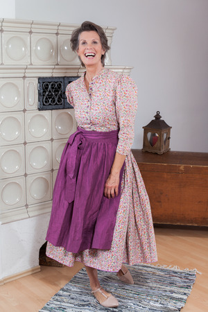 elan: Full length of an elderly woman laughing with great vigor and expressiveness in dirndl in front of a fireplace