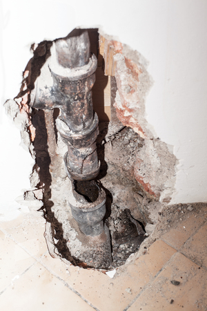 Old sewer pipe made of cast iron, which is broken in the wall