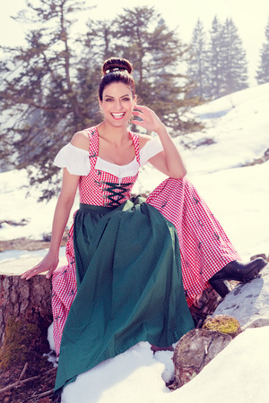 the great outdoors: Pretty model in the Dirndl, smiles in the great outdoors in the camera and presented in the sit your dress