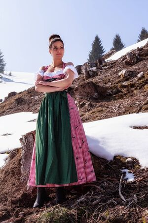 snow fields: Beautiful woman in the Dirndl Dress stands with arms folded in the middle of the Alps between tree stumps and snow fields. Stock Photo