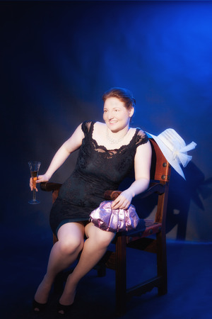 Elegant redhead fat lady in an evening gown, sitting in an old, noble, Spanish wooden chair. Studio recording with blue background Stock Photo