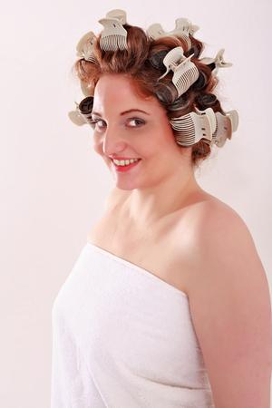 tetona: Retrato de mujer joven y tetona vestida sólo con una toalla y rulos en el pelo sonriendo a la cámara