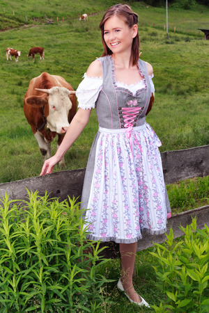 german ethnicity: Portrait of a young peasant woman in dirndl that looks laughing at the camera. Stock Photo