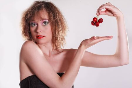 landscape format: Young woman with four red cherries in her hand - landscape format