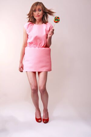 gust: Young woman in pink mini dress frightened as a gust of wind under your skirt blows - Studio shot isolated on gray