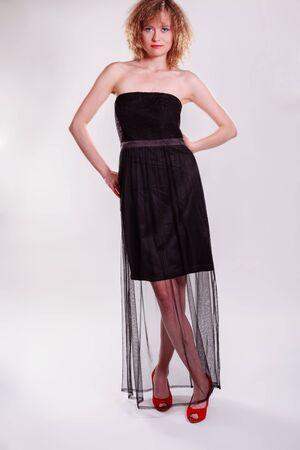 chic woman: A beautiful young woman posing in a chic black dress in an urban setting
