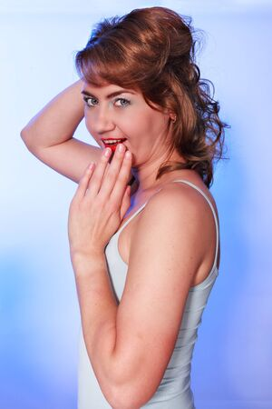 waist shot: Waist portrait of a young attractive woman. Studio shot with blue background
