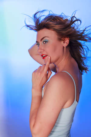 Portrait of a beautiful woman with a lot of enthusiasm and momentum into the camera looking with blue background