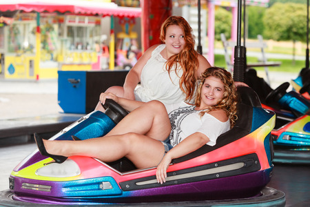 Shot of two young girlfriends with oversize in a bumper car in the fashionable summer outfit.