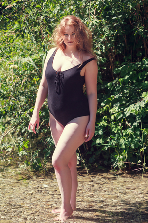 oversize: Model with oversize stands in a bathing suit in the water
