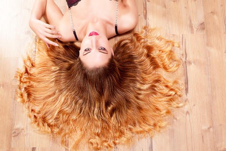 Young woman lying on the ground with diversified blond curly hair and looks into the camera. Stock Photo