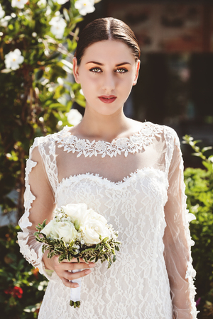 A 34 portrait of a happy new bride holding her boquet on the happiest day of her life