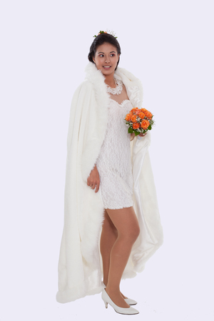 Young bride in short dress, with white cape and bridal bouquet of roses in hand