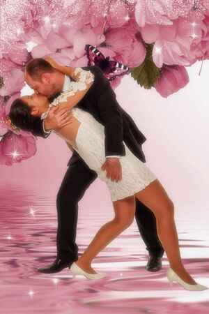 Young married couple kissing while dancing and feeling like on a pink cloud.