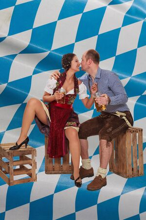 Young woman in the Dirndl flirts with man in leather pants, sitting on wine boxes and Bavarian Diamond pattern in the background
