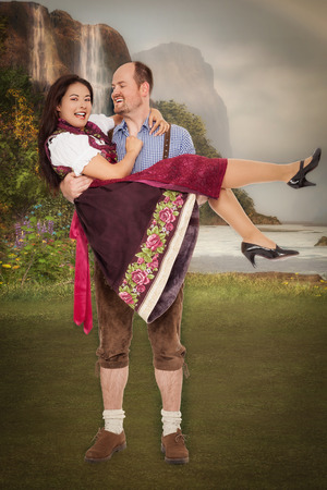 Bavarian man in leather pants wears his girlfriend in the Dirndl Dress on the poor.