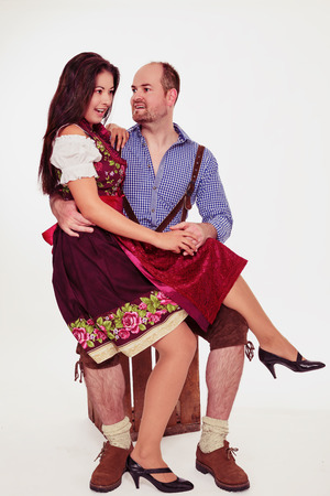 Young woman sitting in mans lap. Bavarian couple in dirndl and leather pants- isolated on white