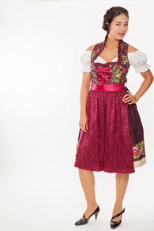 Young woman wearing a Dirndl with copy space - isolated on white. Stock Photo
