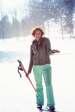 Red-haired young woman has fun with cross-country skiing in the Alps and throws with snow on your winter holiday. Stock Photo