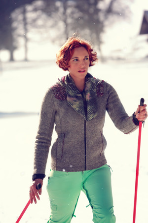 Red-haired young woman recovering in a winter holiday at the cross-country skiing.