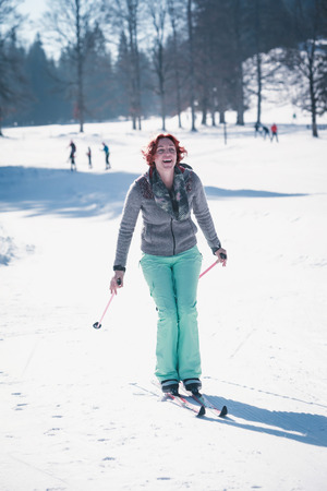 Red-haired young woman has fun with cross-country skiing in the Alps.