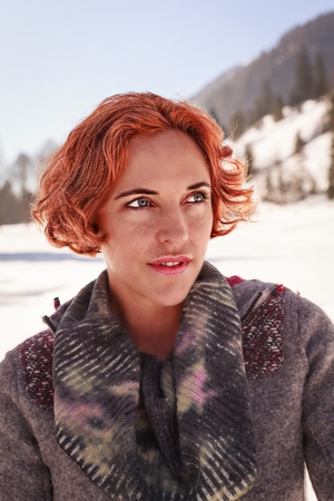 Closeup portrait of a red-haired woman who smiles with winter background Stock Photo