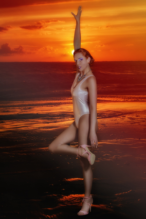 Image of a red-haired woman in a bathing suit, which stretches an arm against sky at sunset on the sea Stock Photo