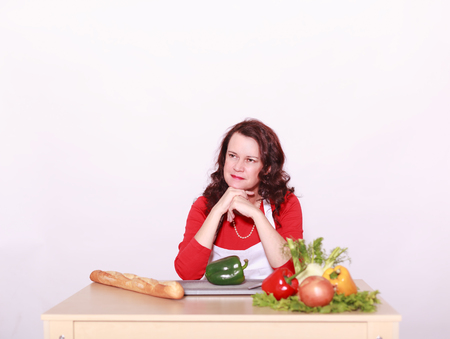 Middle-aged woman sits in front of the vegetables and think about what to cook today.