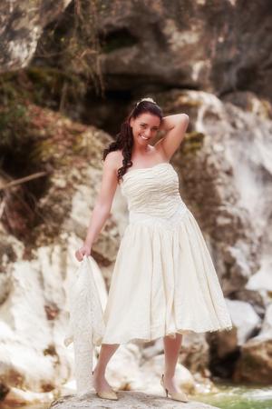 어깨 길이 크림 - 컬러 웨딩 드레스 및 손에 재킷에 젊은 여자가 카메라를 웃는