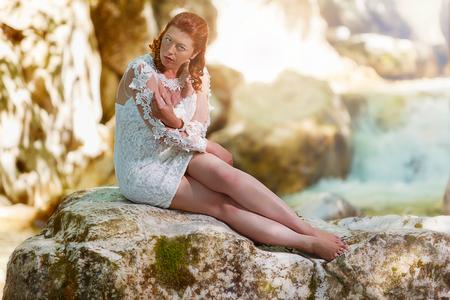 Redhead woman sits with a mini wedding dress