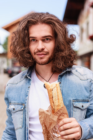 Portrait of a young man with long hair and french baguette in his hand Stock Photo