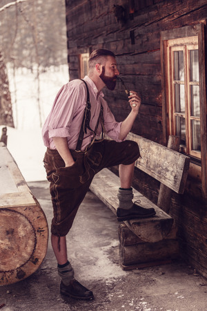 A Bavarian man in lederhosen enjoys his pipe in front of his log cabin in the wilderness