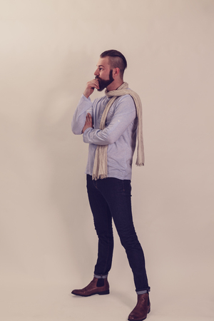 Thoughtful man with beard, fashionable dressed, studio shot