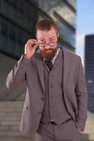 Portrait of business man with a big beard, suit and glasses