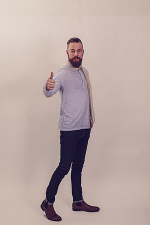 Casual, fashionable dressed man thinking positive with thumbs up.