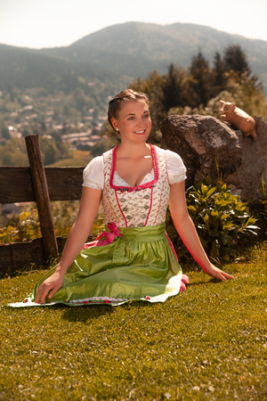 Bavarian young woman in a dirndl sitting on the grass in the sunshine Stock Photo