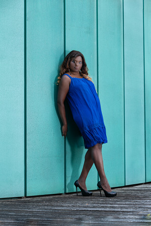 Woman with oversize is leaning against a wall in a summer dress Standard-Bild